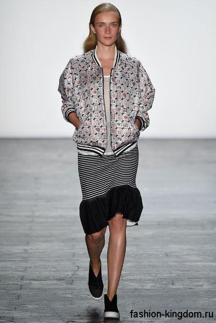 Юбка до колен в стиле кэжуал сочетается со спортивной курткой серо-черной расцветки и черными кедами от Vivienne Tam.