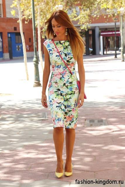Летнее платье-футляр с цветочным рисунком, длиной миди, без рукавов в сочетании с желтыми туфлями на каблуке.