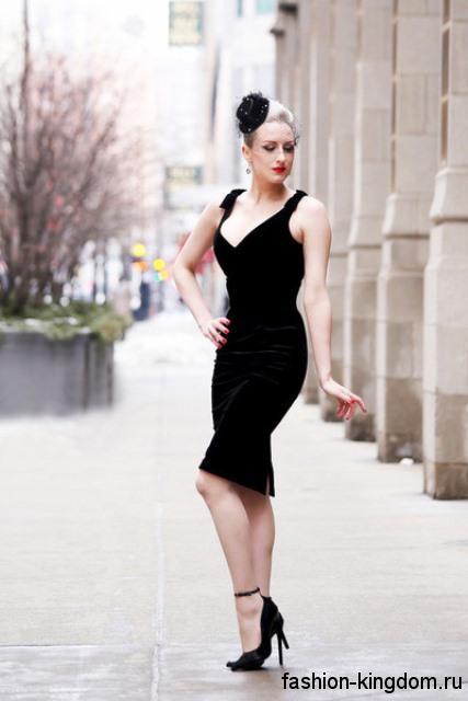 Черное платье-футляр приталенного кроя, длиной до колен, без рукавов сочетается с туфлями черного цвета на каблуке.
