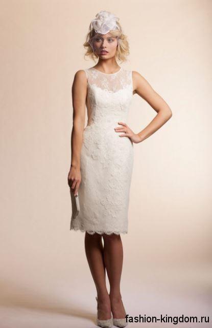 Свадебное платье-футляр белого цвета, с гипюровыми вставками, без рукавов, длиной до колен в сочетании с белыми туфлями на каблуке.