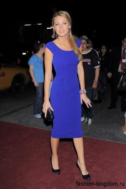 Вечернее платье-футляр синего цвета, длиной ниже колен, без рукавов в тандеме с клатчем и туфлями черного тона.