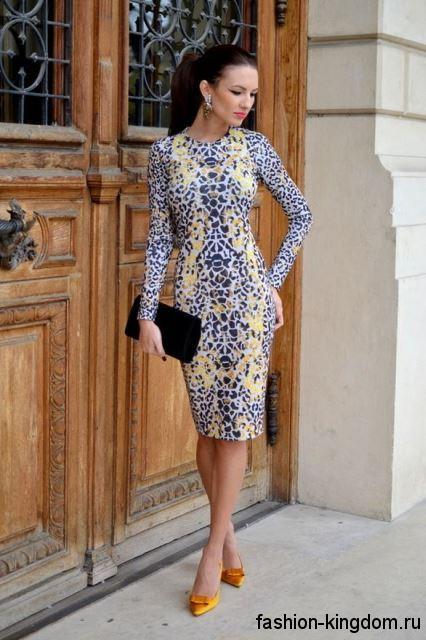 Платье-футляр серого тона с леопардовым принтом, длиной до колен, с длинными рукавами в тандеме с золотистыми туфлями.
