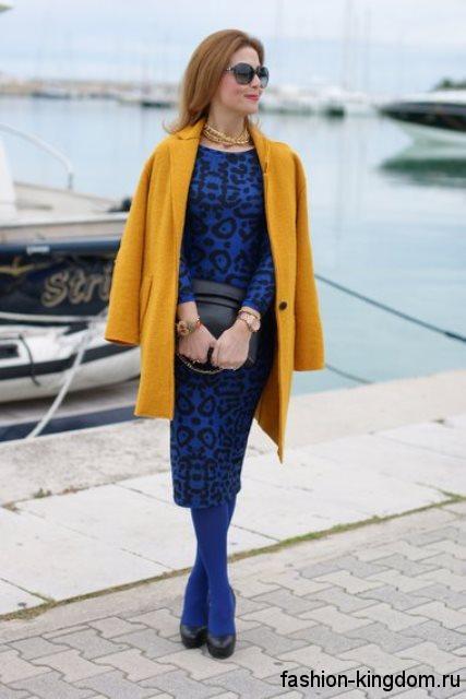 Платье-футляр синего цвета с черным принтом, приталенного кроя в тандеме с демисезонным пальто и золотыми украшениями.