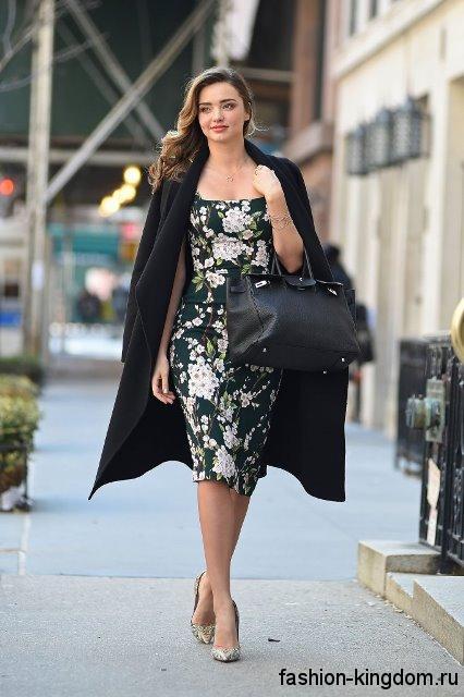 Платье-футляр с цветочным рисунком, длиной до колен дополняется демисезонным черным пальто и серебристыми туфлями на каблуке.