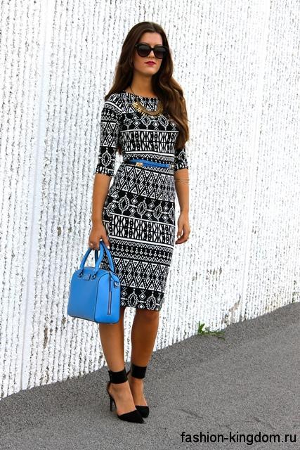Платье-футляр черно-белого тона с геометрическим рисунком, с рукавами до локтей в тандеме с черными туфлями на каблуке.