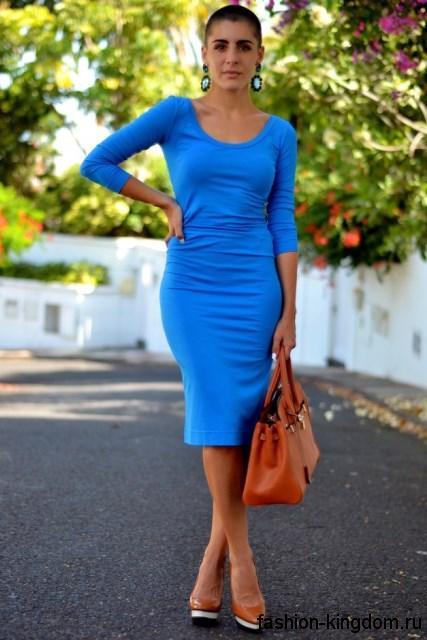 Платье-футляр голубого цвета, приталенного кроя, с рукавами три четверти в тандеме с сумкой и туфлями рыжего тона.