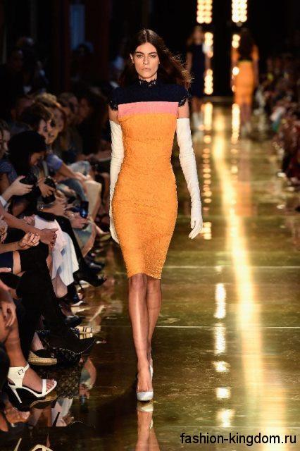 Платье-футляр оранжевого оттенка, длиной до колен, с короткими рукавами и длинными перчатками от Alex Perry.