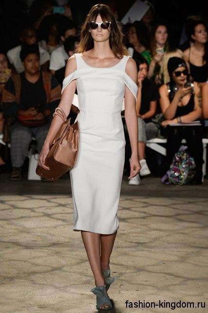 Белое платье-футляр без рукавов, приталенного кроя в сочетании с коричневой сумочкой из коллекции Christian Siriano.