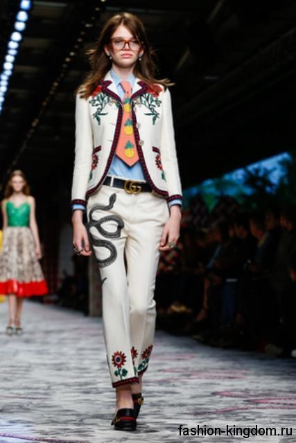 Брючный костюм белого цвета с цветочным и звериным принтом в тандеме с кожаным ремнем и оранжевым галстуком из коллекции весна-лето 2016 от Gucci.
