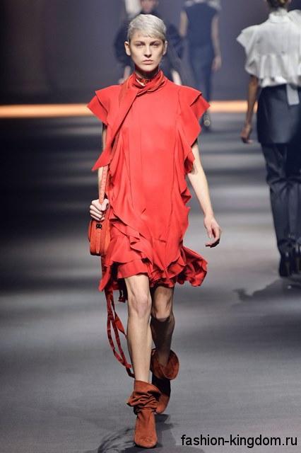 Короткое платье с оборками красного цвета сочетается с ботильонами на каблуке из коллекции весна-лето 2016 от Lanvin.