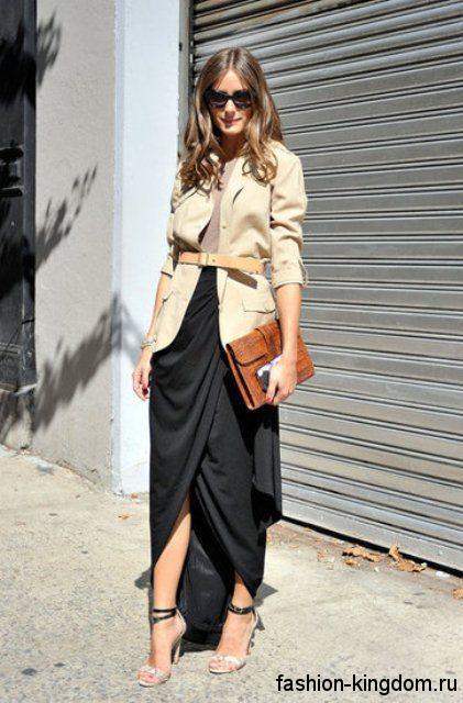 Асимметричная юбка макси черного цвета сочетается с жакетом бежевого тона, коричневым клатчем и туфлями на шпильке.