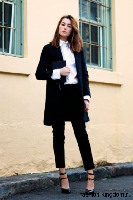 Офисная белая блузка с длинными рукавами и воротником-стойкой в тандеме с брючным костюмом черного цвета.