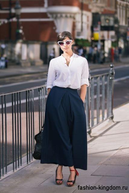 Белая блузка с рукавами до локтей, свободного фасона в сочетании с длинной темно-синей юбкой и открытыми туфлями на платформе.