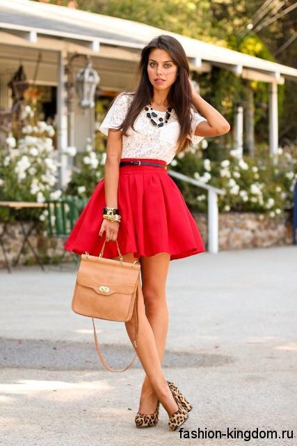 Гипюровая белая блузка с короткими рукавами сочетается с короткой красной юбкой-плиссе и туфлями с леопардовым принтом.