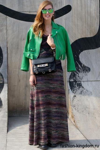 Короткая кожаная куртка зеленого цвета сочетается с длинным платьем серо-фиолетового тона в полоску.
