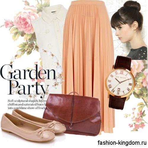 Юбка макси персикового цвета, свободного кроя дополняется белой рубашкой без рукавов и балетками бежевого оттенка.