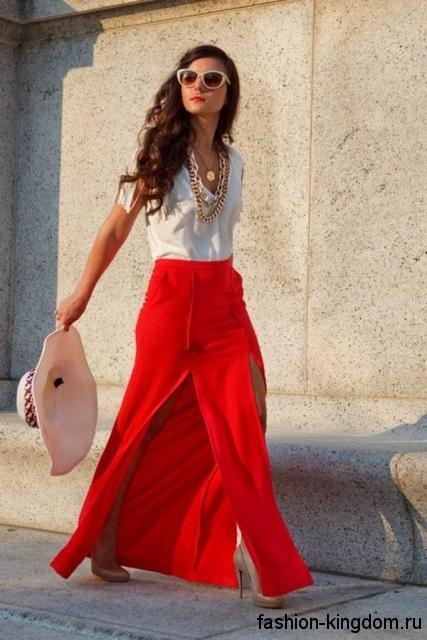 Юбка макси красного цвета с высокими разрезами и завышенной талией в тандеме с белой блузкой и туфлями на каблуке.