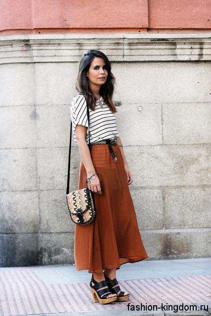 Легкая юбка макси рыжего оттенка, трапециевидного кроя сочетается с блузой черно-белой расцветки в полоску.