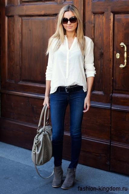 Шифоновая белая блузка с длинными рукавами, прямого кроя сочетается с узкими синими джинсами и серыми ботильонами на каблуке.