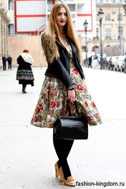 Женская кожаная куртка черного цвета в сочетании с пышным платьем до колен, с цветочным рисунком.