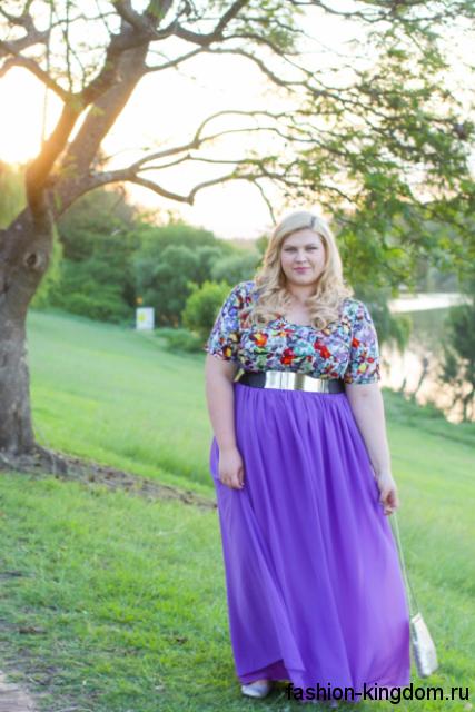 Шифоновая юбка макси фиолетового цвета с широким поясом для полных сочетается с блузкой с цветочным принтом и короткими рукавами.