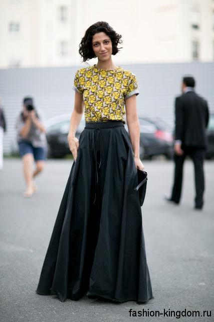 Черная юбка макси расширенного фасона сочетается с блузкой желто-серой расцветки и клатчем черного тона.