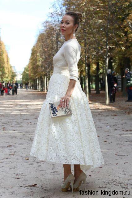 Вечерняя юбка макси белого цвета с ажурной отделкой сочетается с блузой молочного оттенка и туфлями на каблуке.