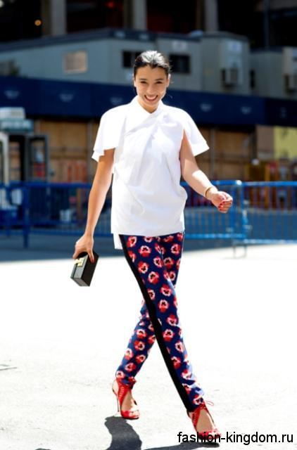 Летняя белая блузка с короткими рукавами, прямого покроя дополняются брюками с цветочным принтом и красными босоножками на каблуке.
