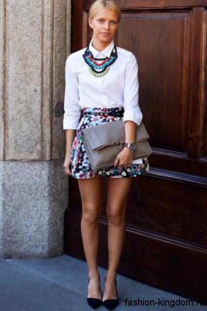 Белая блузка с рукавами три четверти для вечернего образа в тандеме с короткой юбкой с цветочным принтом и черными туфлями.