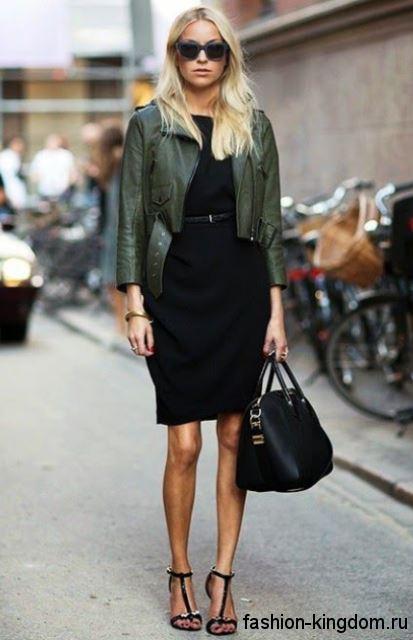 Укороченная кожаная куртка темно-зеленого цвета гармонирует с платьем-футляр черного тона и босоножками на каблуке.