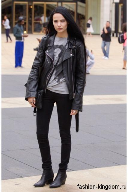 Кожаная куртка-косуха черного цвета дополняется узкими черными брюками и футболкой серого тона.