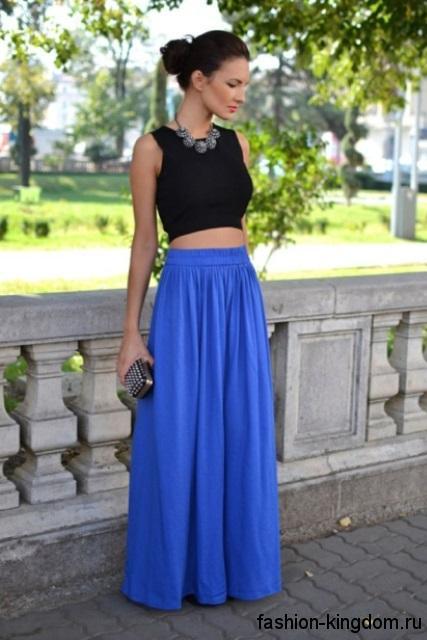 Летняя юбка макси синего цвета, свободного кроя гармонирует с коротким черным топом без рукавов.