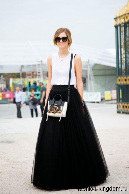 Пышная юбка макси черного цвета в сочетании с блузкой белого тона без рукавов и сумочкой черно-белой расцветки.