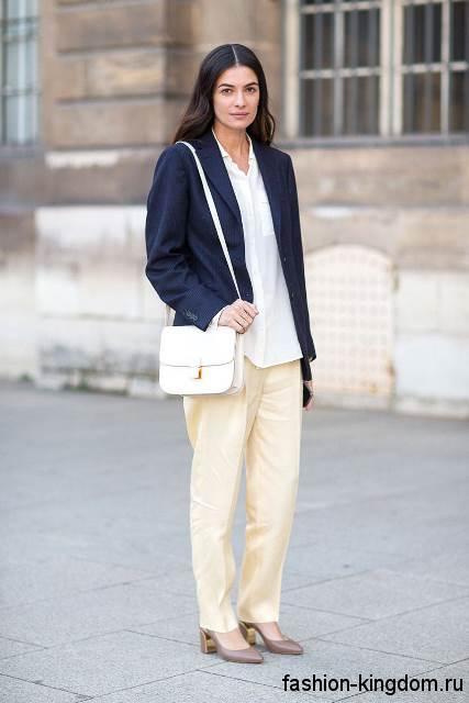 Длинная белая блузка с накладными карманами дополняется пиджаком темно-синего тона и бежевыми классическими брюками.