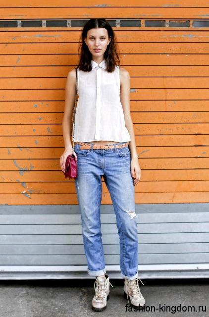 Короткая белая блузка без рукавов, свободного кроя в тандеме с джинсами-бойфрендами голубого цвета и серыми ботинками.