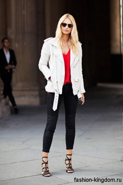 Удлиненная кожаная куртка белого цвета гармонирует с узкими черными брюками и босоножками на шпильке.