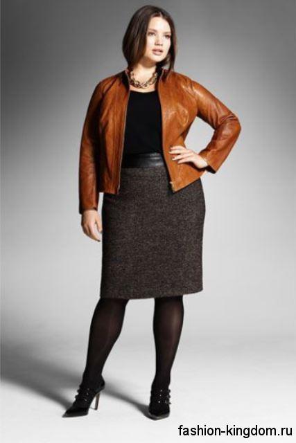 Кожаная куртка рыжего цвета прямого фасона дополняется юбкой-миди темно-серого тона и черной блузкой.