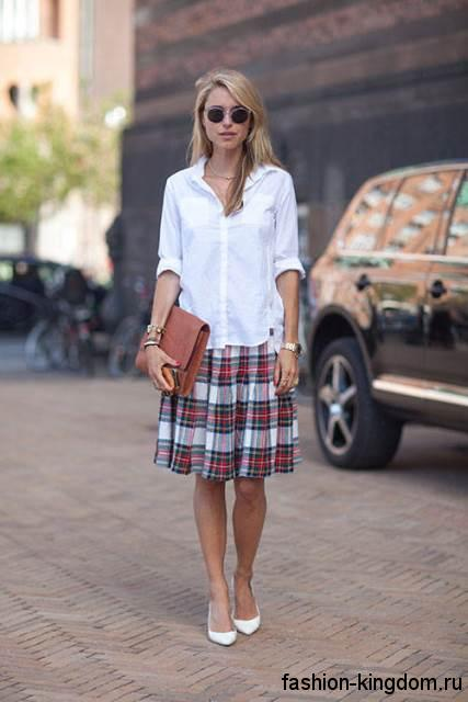Офисная белая блузка с рукавами до локтей, прямого кроя в тандеме с юбкой-миди в клетку и белыми туфлями на каблуке.