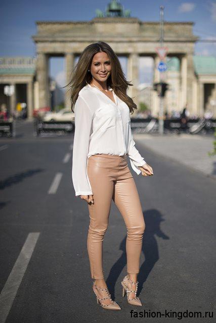 Шифоновая белая блузка с длинными рукавами сочетается с кожаными брюками бежевого цвета и открытыми туфлями на каблуке.