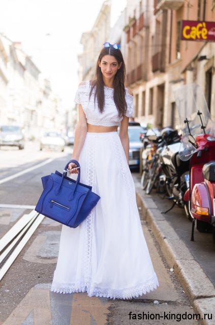 Летняя юбка макси белого цвета с оборками сочетается с коротким белым топом и сумочкой синего тона.
