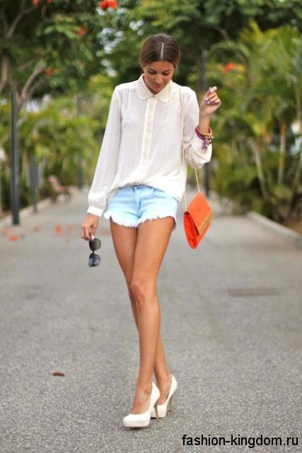 Шифоновая белая блузка свободного фасона, с длинными рукавами гармонирует с голубыми джинсовыми шортами и белыми туфлями на каблуке.
