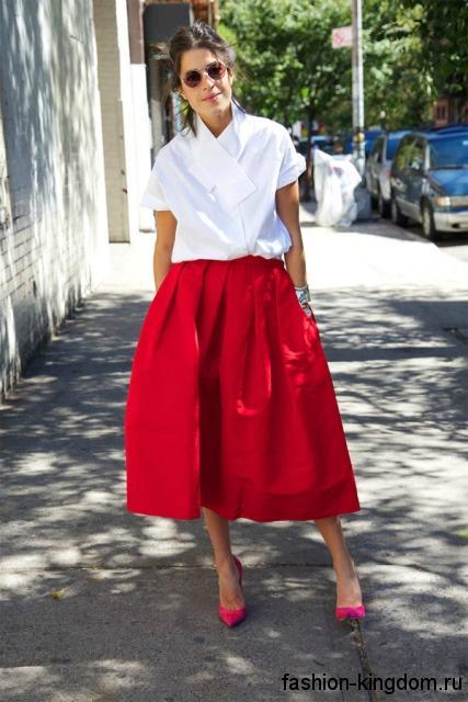 Белая блузка широкого фасона, с короткими рукавами дополняется длинной красной юбкой и розовыми туфлями на каблуке.