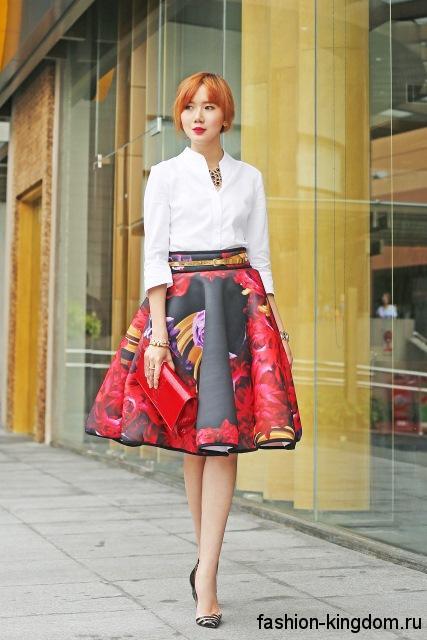 Белая блузка прямого фасона, с рукавами три четверти сочетается с пышной юбкой красно-черной расцветки и туфлями на каблуке.