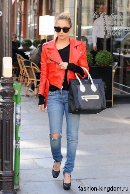 Короткая кожаная куртка красного цвета сочетается с рваными джинсами голубого тона и туфлями на каблуке.