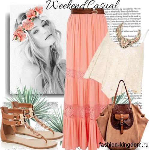 Летняя юбка макси кораллового цвета с ажурными вставками и кожаным поясом в сочетании с ажурным бежевым топом.