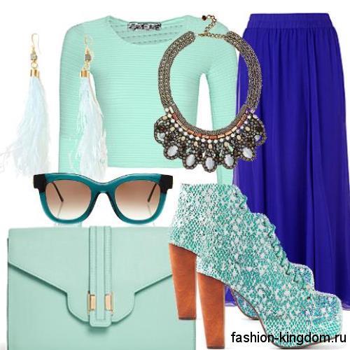 Синяя юбка макси свободного кроя гармонирует с короткой блузкой, клатчем и ботильонами бирюзовой расцветки.