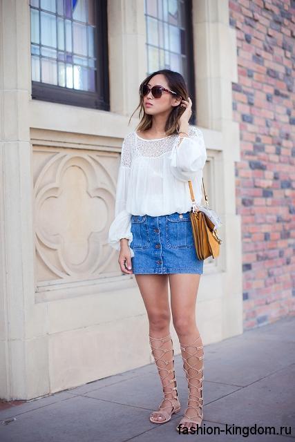 Легкая белая блузка с длинными рукавами и ажурными вставками сочетается с короткой джинсовой юбкой и босоножками-гладиаторами.