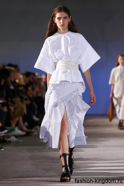Белая блузка свободного кроя, с широкими рукавами до локтей в сочетании с белой юбкой-миди из коллекции Cedric Charlier.