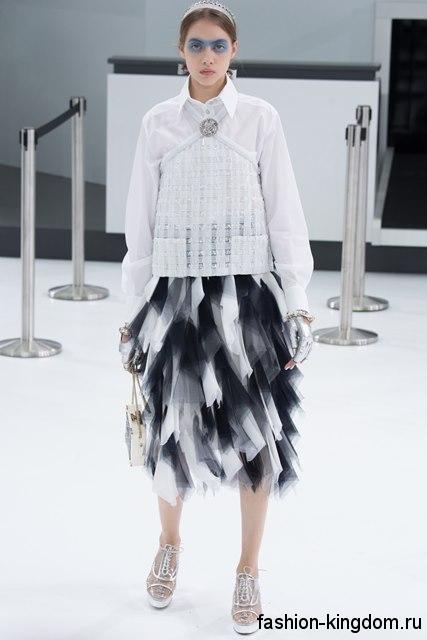 Белая блузка с длинными рукавами, прямого кроя, с ажурными вставками в тандеме с черно-белой юбкой от Chanel.