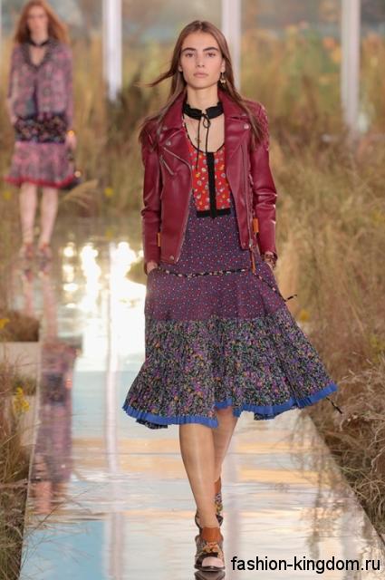 Женская кожаная куртка бордового оттенка в сочетании с платьем с цветочным принтом из коллекции Coach.